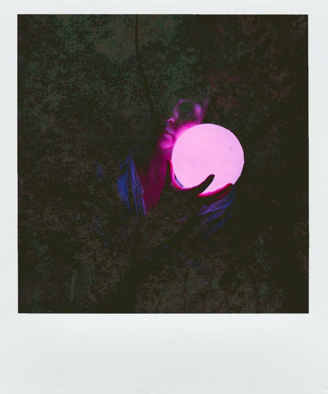 Buch Thema finden - Polaroidbild, auf dem ein Mädchen eine Leuchtkugel hält