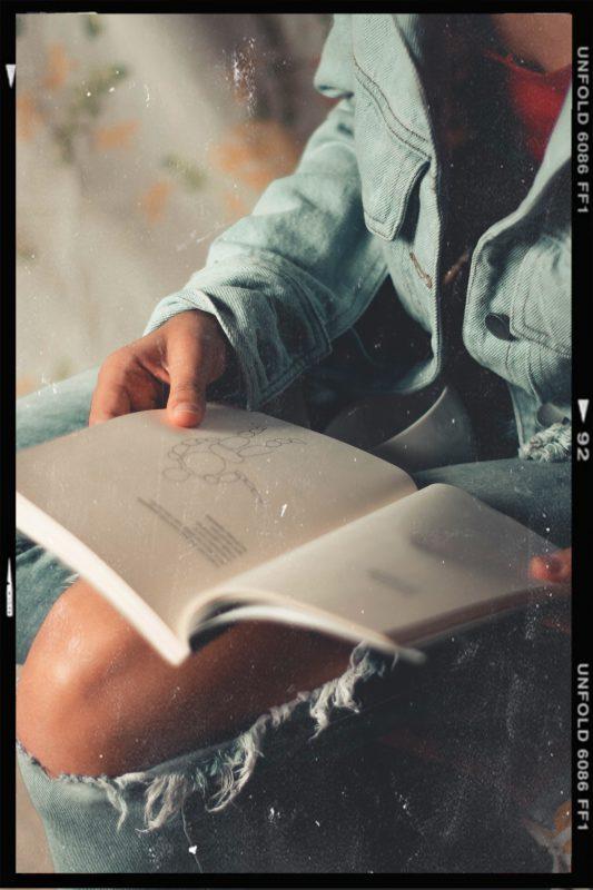 Plot für ein Buch schreiben - Jemand schaut in ein Buch uns lässt sich inspirieren