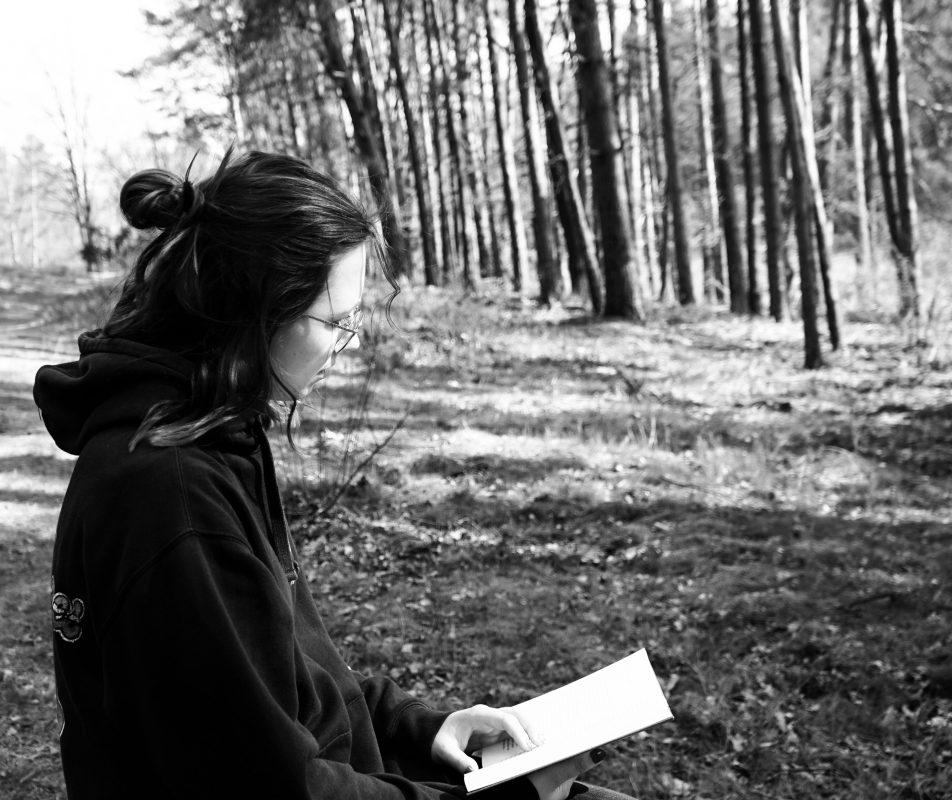 Frau die im Wald sitzt und ließt