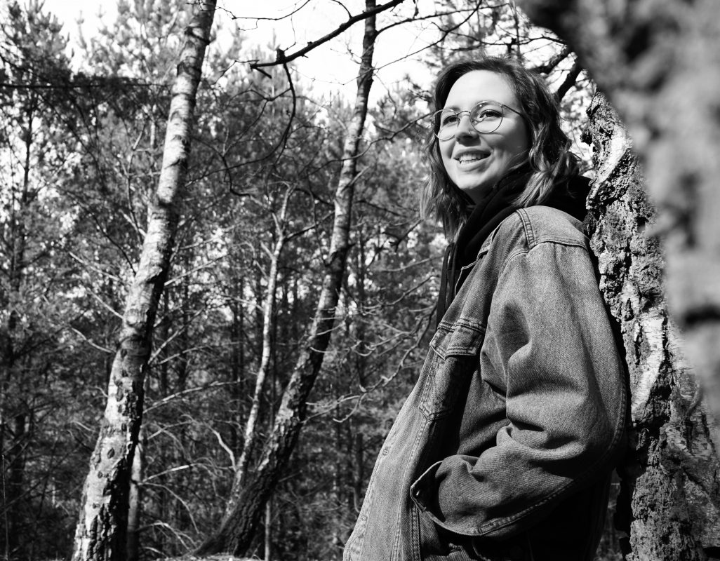 Frau die an einem Baum lehnt und herzlich lacht