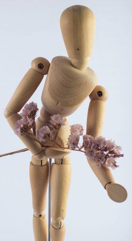 Holzfigur mit Blumenstrauß als Inspiration um Roman Figuren erstellen zu können