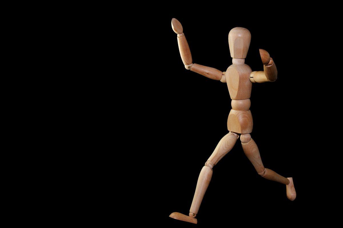 Figur aus Holz die rennt um die Dynamik von Roman Figuren entwickeln zu können