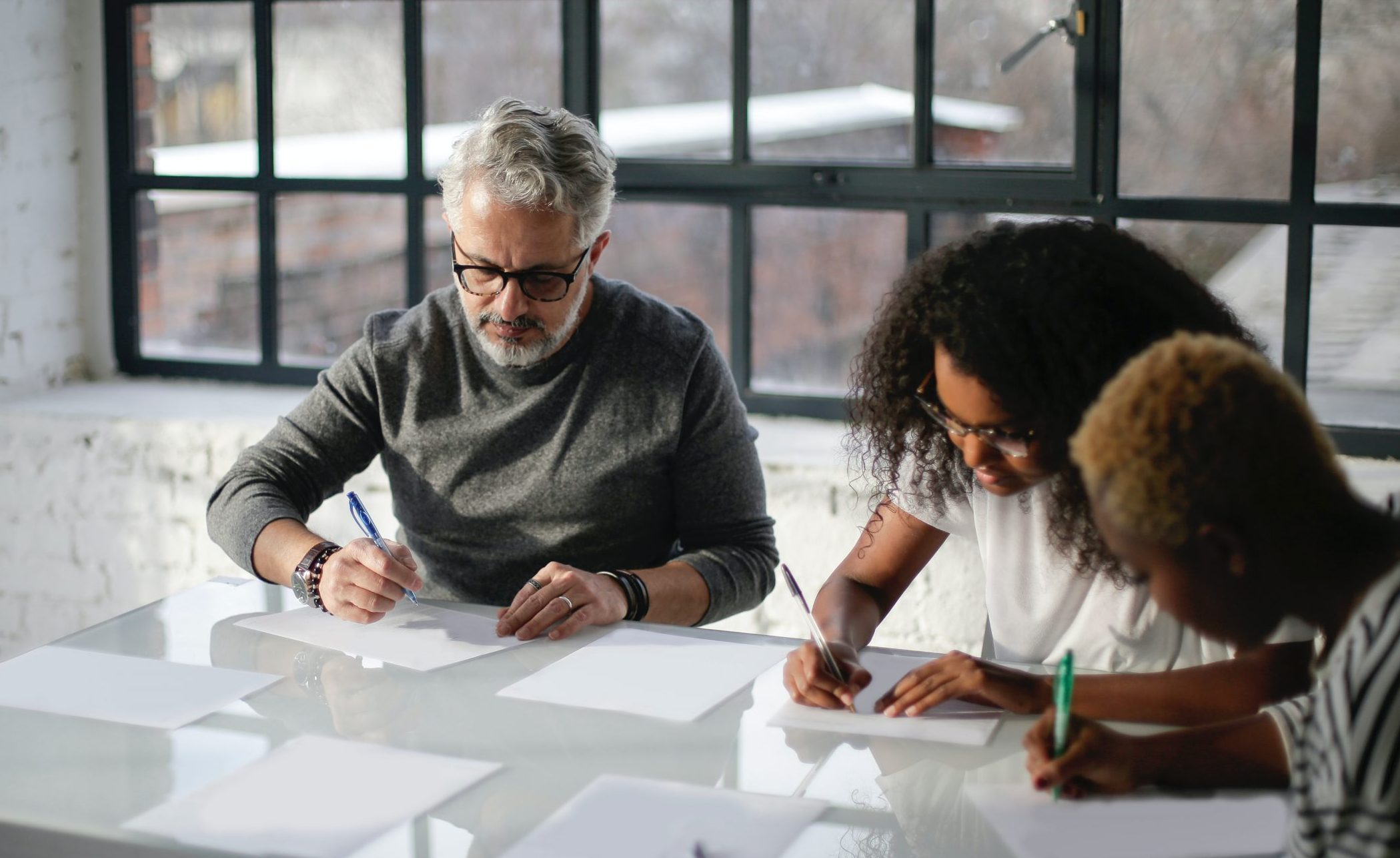Menschen schreiben gemeinsam an einem Tisch