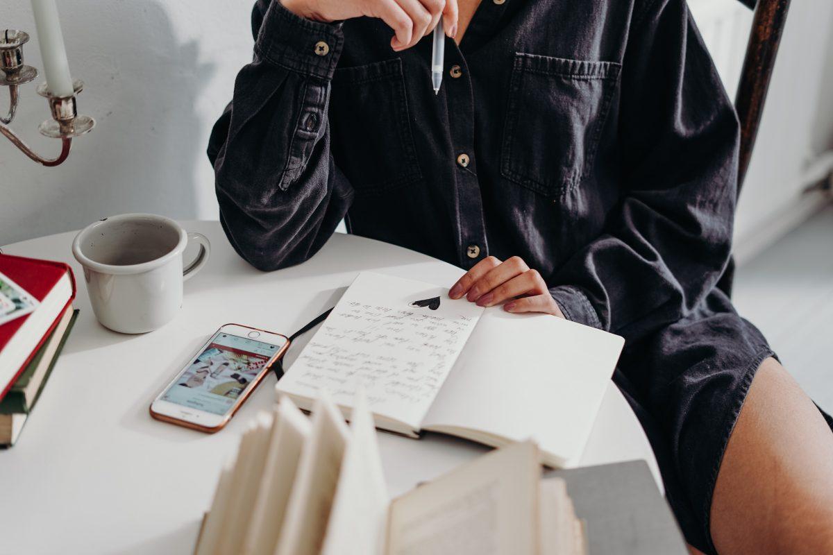Frau plant am Schreibtisch in ihrem Notizbuch