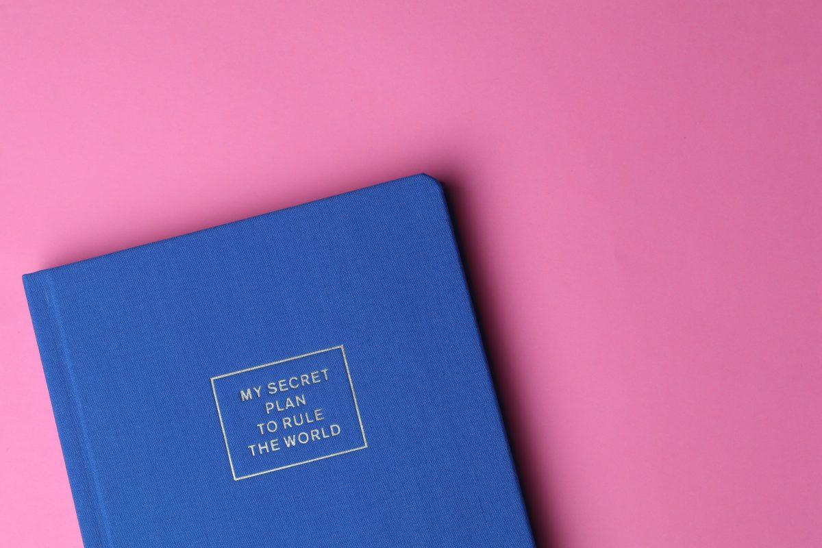 Taschenkalender auf pinkem Tisch