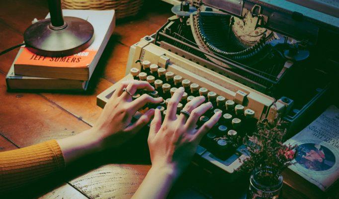 Jemand schreibt auf einer Schreibmaschine