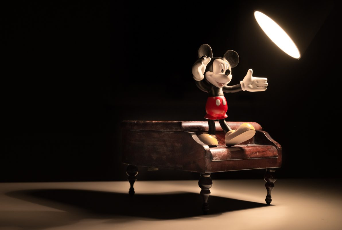 Figur Mickey Mouse tanzt auf einem Klavier und dient zur Inspiration um als Autor Roman Figuren entwickeln zu können