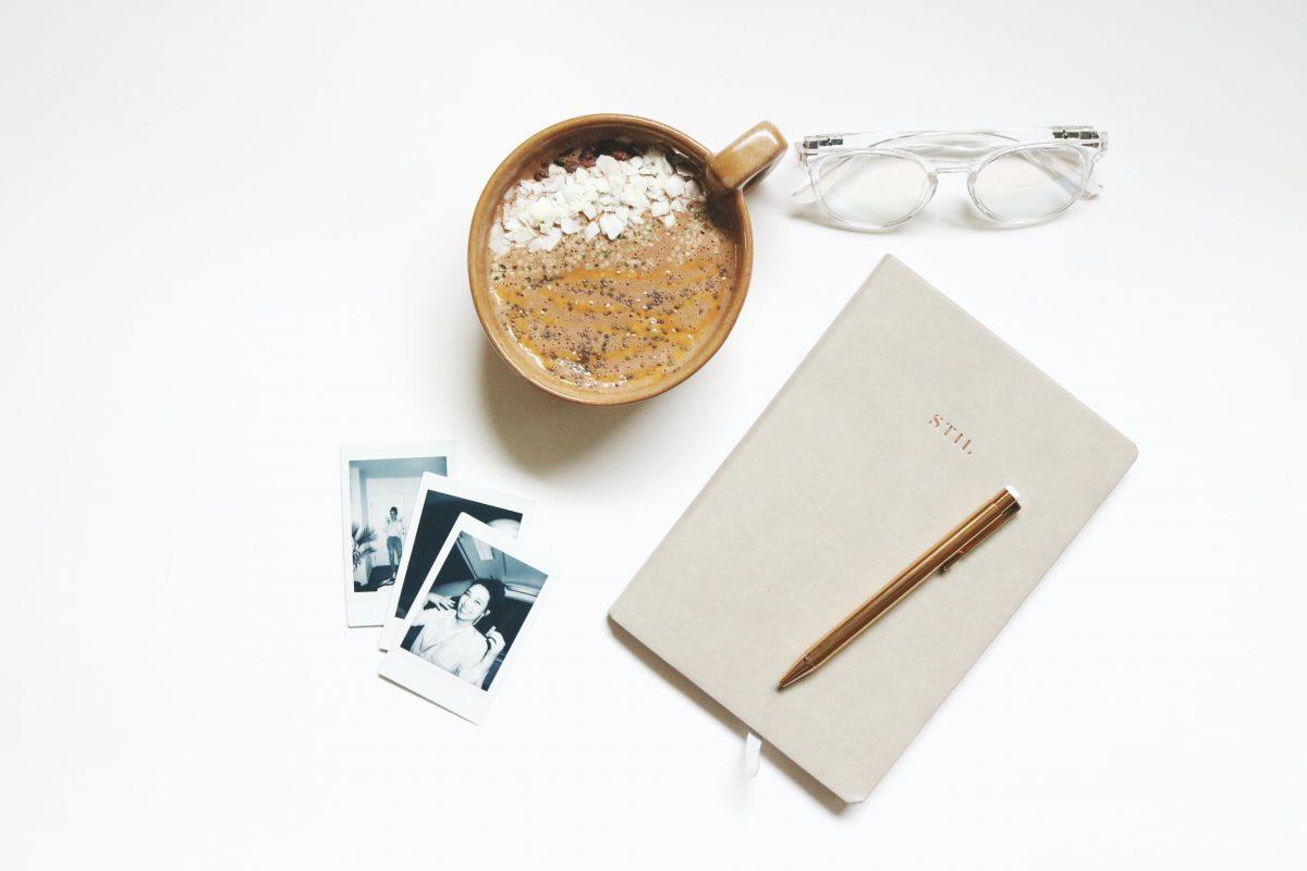 Schreibtisch mit Projektbuch, Fotos und einer Kaffeetasse um kreativ Geschichten schreiben zu können