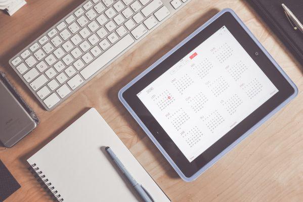 Schreibtisch mit Notizblock und Kalenderansicht eines Tablets