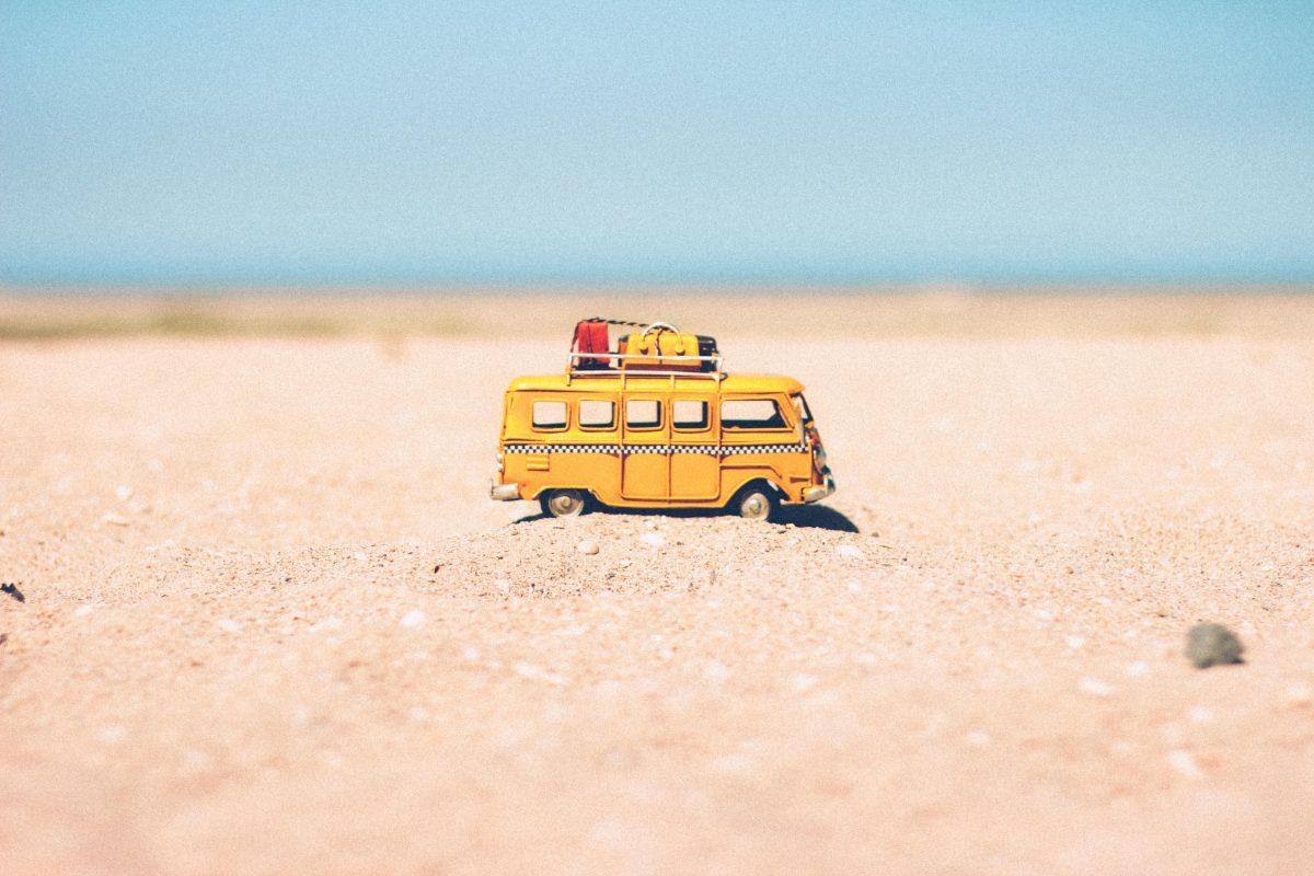 Spielzeugreisebus im Sand als Symbol für Kreatives Schreiben im Urlaub